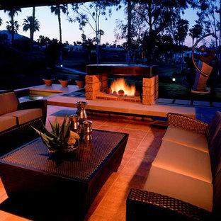 Foto di un grande patio o portico design dietro casa con un focolare, piastrelle e un tetto a sbalzo