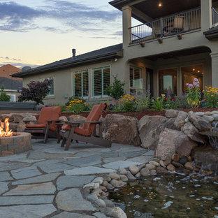 Foto di un patio o portico stile rurale di medie dimensioni e dietro casa con un focolare, pavimentazioni in pietra naturale e nessuna copertura