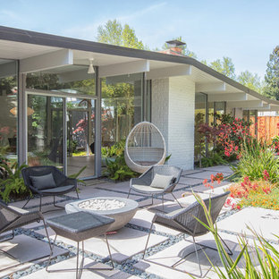Example of a 1950s backyard concrete patio design in San Francisco with a fire pit and no cover