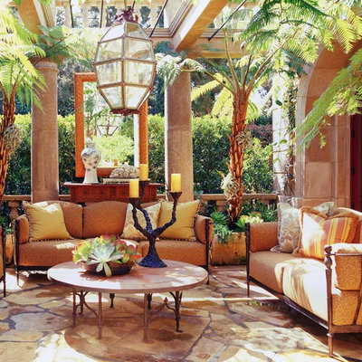Example of a tuscan stone patio design in Orange County with a pergola