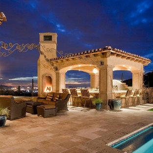 Esempio di un ampio patio o portico mediterraneo dietro casa con un focolare e pavimentazioni in pietra naturale