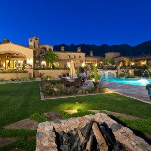Foto di un ampio patio o portico mediterraneo dietro casa con un focolare e pavimentazioni in pietra naturale