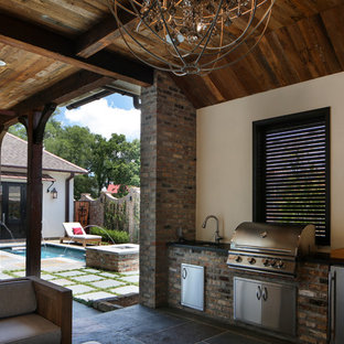 Mid-sized transitional courtyard stone patio kitchen photo in New Orleans with a roof extension