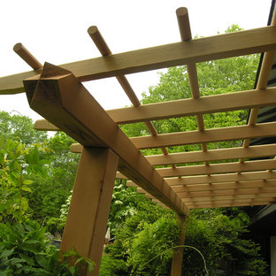 This is an example of a large asian backyard patio in Philadelphia with a pergola.