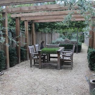 Ispirazione per un patio o portico country con ghiaia e una pergola