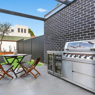 Photo of a contemporary backyard patio in Sydney with tile and a pergola.