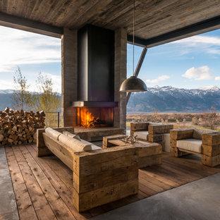 Ispirazione per un ampio patio o portico rustico dietro casa con un focolare, lastre di cemento e un tetto a sbalzo