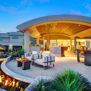 Idee per un ampio patio o portico moderno dietro casa con un tetto a sbalzo, un focolare e pavimentazioni in cemento