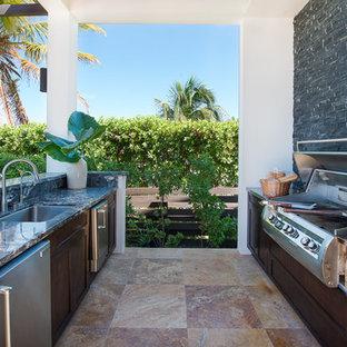 Diseño de patio tropical con cocina exterior y pérgola