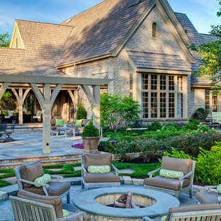 Elegant backyard patio photo in Chicago with a fire pit and a pergola