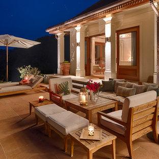 Immagine di un patio o portico etnico di medie dimensioni e dietro casa con pavimentazioni in pietra naturale e un parasole
