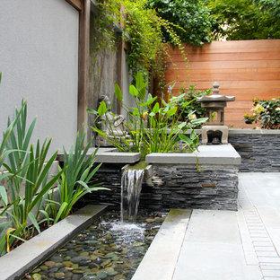 Inspiration för en liten orientalisk gårdsplan, med en fontän och naturstensplattor