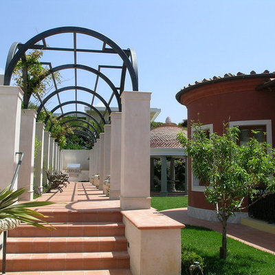 Example of a tuscan tile patio design in Orange County with a pergola