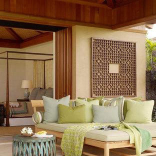 Ispirazione per un patio o portico tropicale con un tetto a sbalzo