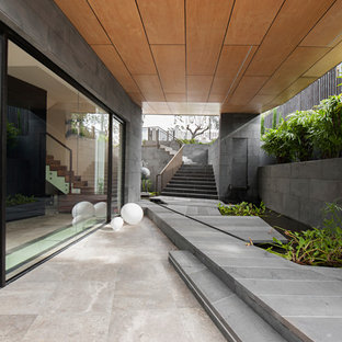 Inspiration for a contemporary patio in Sydney with a water feature, tile and a roof extension.