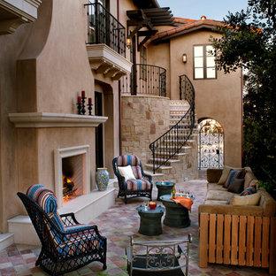 Esempio di un patio o portico mediterraneo con pavimentazioni in cemento, nessuna copertura e un caminetto