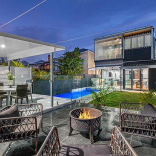 Design ideas for a contemporary backyard patio in Brisbane with a fire feature.