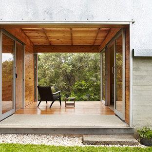 Idee per un piccolo patio o portico industriale dietro casa con pedane e un tetto a sbalzo