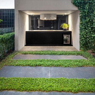 Photo of a contemporary patio in Melbourne with an outdoor kitchen, natural stone pavers and a roof extension.