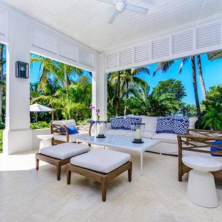 Idee per un grande patio o portico tropicale dietro casa con piastrelle e un tetto a sbalzo