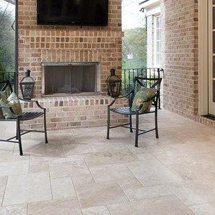 Idee per un patio o portico stile americano di medie dimensioni e dietro casa con un focolare, piastrelle e un tetto a sbalzo