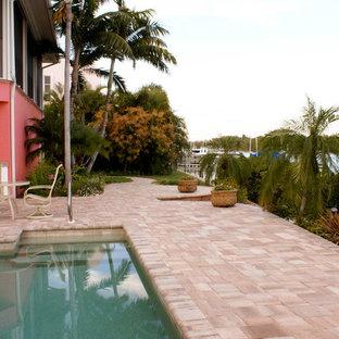 Idee per un grande patio o portico tropicale dietro casa con nessuna copertura