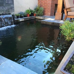 Ispirazione per un patio o portico etnico di medie dimensioni e dietro casa con fontane, piastrelle e una pergola