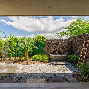 Idée de décoration pour une terrasse avec une douche extérieure arrière ethnique de taille moyenne avec des pavés en pierre naturelle et aucune couverture.