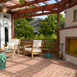 Elegant brick patio photo in San Diego with a fire pit and a pergola