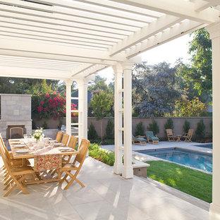 Idée de décoration pour une terrasse tradition avec un foyer extérieur et une pergola.