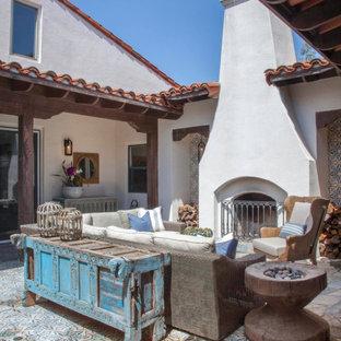 Ispirazione per un patio o portico mediterraneo con un caminetto, piastrelle e nessuna copertura