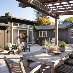 This is an example of a mid-sized transitional backyard patio in San Francisco with a fire feature and a pergola.