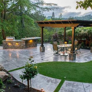 Ispirazione per un patio o portico mediterraneo di medie dimensioni e dietro casa con cemento stampato e una pergola