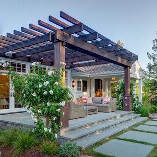 Foto di un patio o portico country dietro casa con una pergola