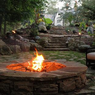 Immagine di un ampio patio o portico eclettico dietro casa con un focolare, pavimentazioni in pietra naturale e nessuna copertura