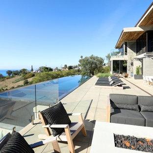 Ispirazione per un ampio patio o portico design dietro casa con un caminetto, pavimentazioni in cemento e nessuna copertura
