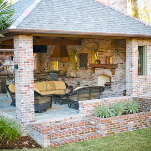 Photo of a large mediterranean back patio in New Orleans with an outdoor kitchen, brick paving and a gazebo.