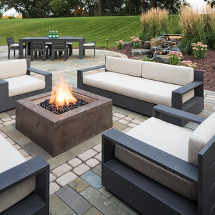 Example of a mid-sized trendy backyard concrete paver patio design in Minneapolis with a fire pit and no cover