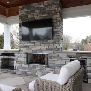 Large elegant backyard concrete paver patio photo in Louisville with a fireplace and a roof extension