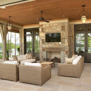 Идея дизайна: большой дворик на заднем дворе в классическом стиле с местом для костра, покрытием из каменной брусчатки и навесом