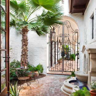 Example of a tuscan courtyard patio fountain design in Austin