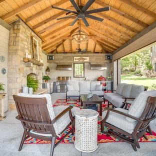 Ispirazione per un ampio patio o portico stile rurale con lastre di cemento e un tetto a sbalzo