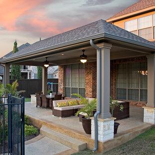 Ispirazione per un patio o portico contemporaneo dietro casa e di medie dimensioni con cemento stampato e un tetto a sbalzo