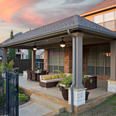 Mid-sized trendy backyard stamped concrete patio photo in Dallas with a roof extension