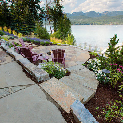 Mid-sized trendy backyard stone patio photo in Other with a fire pit and no cover