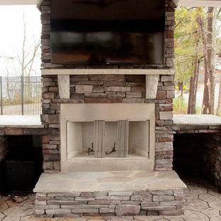 Immagine di un patio o portico rustico di medie dimensioni e dietro casa con un focolare, un tetto a sbalzo e cemento stampato