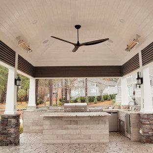 Immagine di un patio o portico stile rurale di medie dimensioni e dietro casa con un focolare, un tetto a sbalzo e cemento stampato