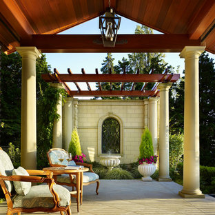 Example of a huge tuscan backyard concrete paver patio container garden design in Seattle with a roof extension