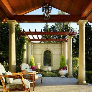 Foto di un ampio patio o portico mediterraneo dietro casa con un giardino in vaso, pavimentazioni in cemento e un tetto a sbalzo