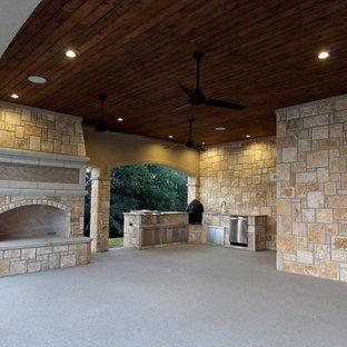 Esempio di un grande patio o portico mediterraneo dietro casa con un focolare, graniglia di granito e un tetto a sbalzo
